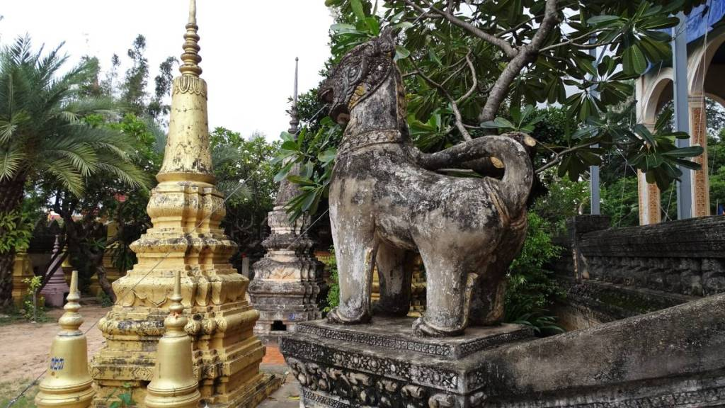 A characteristic statue of a lion and some stupas at the temple in Siem Reap
