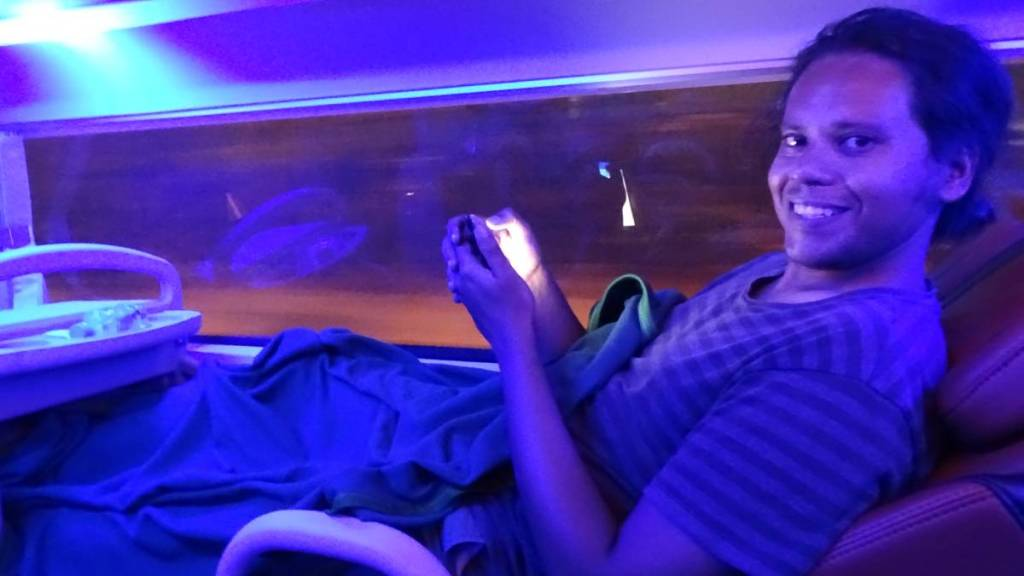 Sayak illuminated with the blue light inside a Vietnamese sleeper bus , covered with a blanket
