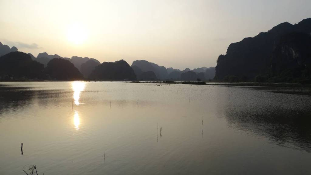 The sun setting over a pond in the karst lanscape of Tam Coc in Vietnam