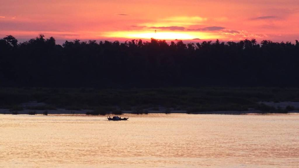 Sunset over the forested bank of Mekong in Kratie, Cambodia