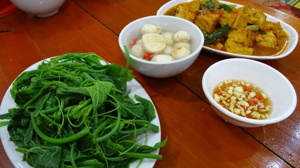 A plate of boiled greens, a bowl of pickles and a large tray of tofu in a sauce - vegan options in Vietnam