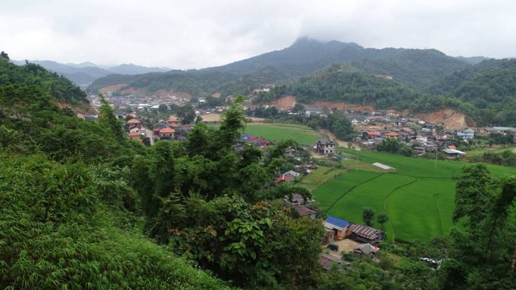 A view from the bus station in Sam Neua onto the fringes of the town, paddy fields and mist covered mountains in the background