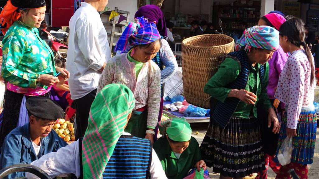 Women at the Meo Vac market in Vietnam wearing brightly coloured head scarves and skirts, some carrying woven baskets.