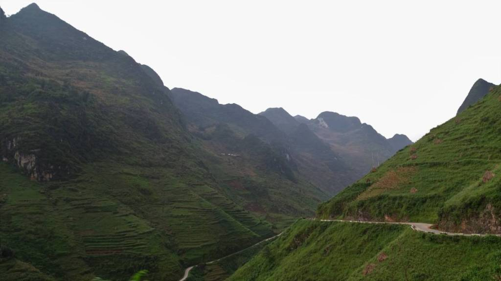 A deep canyon between steep, sharp-ended and grass covered mountains and a narrow road cut in the side of the mountain at the start of Ma Pi Leng pass in Ha Giang