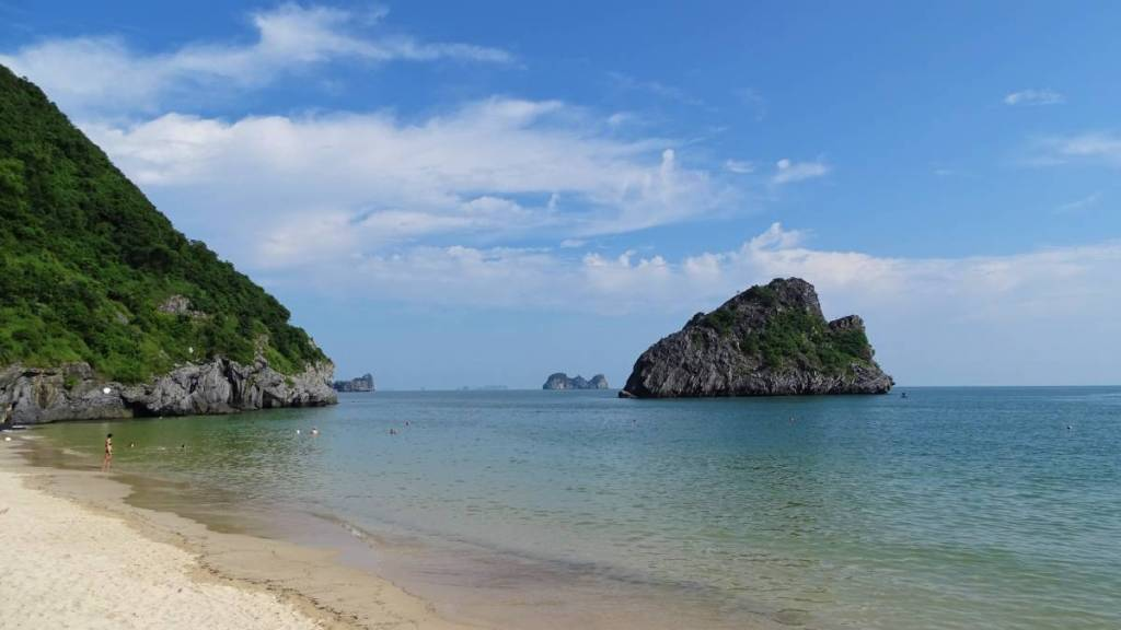 Cat Ba beach: white sand, light blue water and the karst cliffs and  karst rocks in the sea