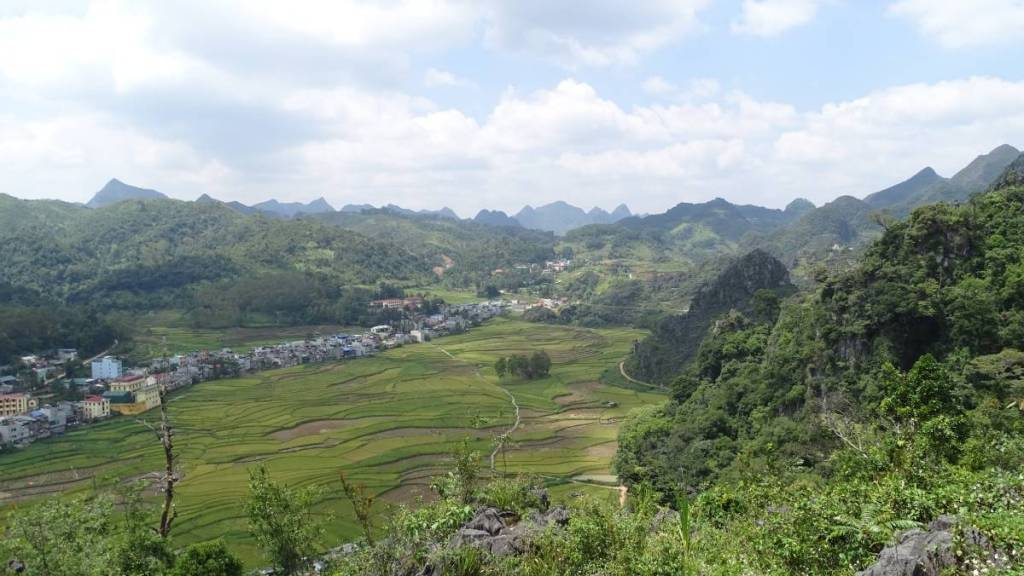 View from Don Cao fortress in Dong Van at the wide valley filled with rice paddies and a string of houses and surrounded with the limestone mountains