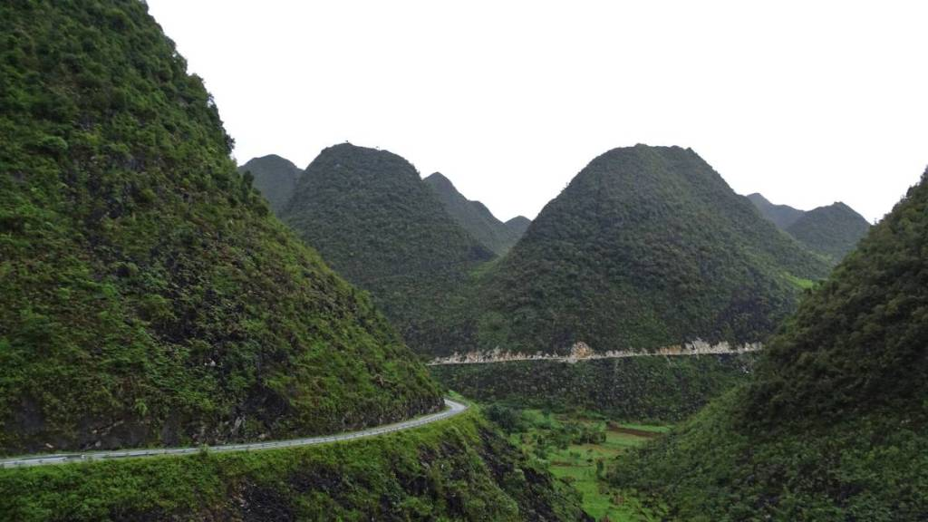 A winding road cut in the conical, steep, deep green mountains filling up the landscape till the horizon at the Dong Van Karst Plateau