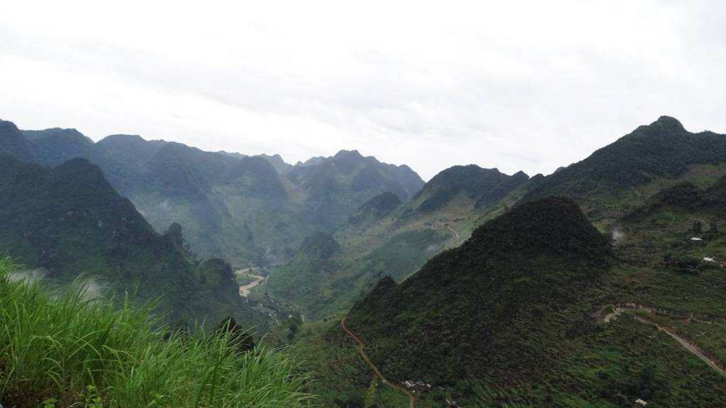 The view at the deep valley and surrounding sharp-ended, green mountains taking from a bus on the road from Dong Van to Ha Giang
