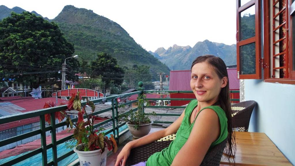 The author sitting at the terrace of a guesthouse in Meo Vac, a sharp-ended mountains in the background