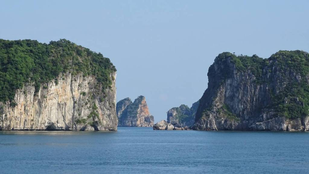 Steep, vertical white karst rocks covered with greenery rising from the sea in Ha Long Bay
