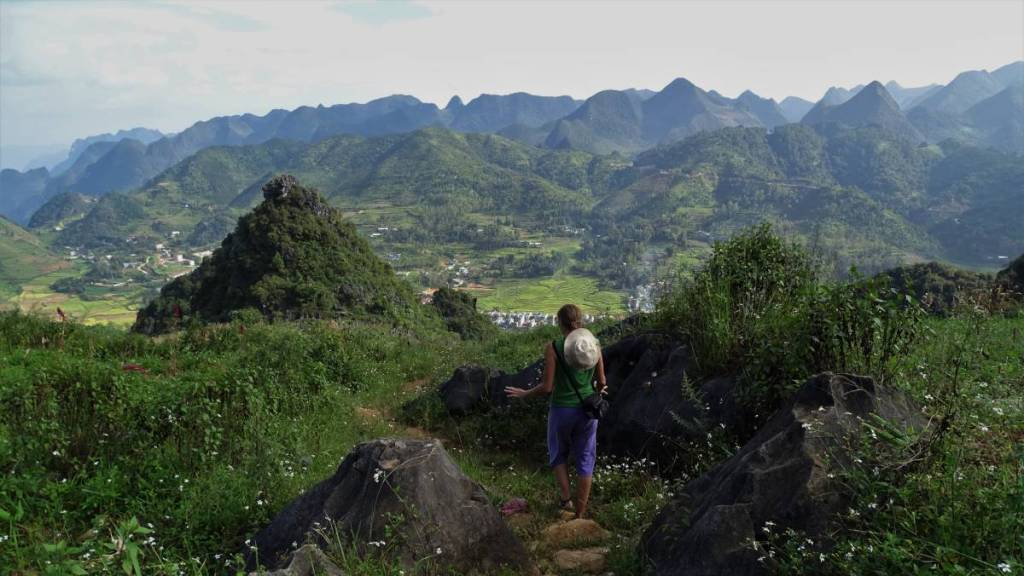 The author walking down the narrow path among the rocks with a panoramic view at the mountains and the valley where Dong Van is located opening in front of her