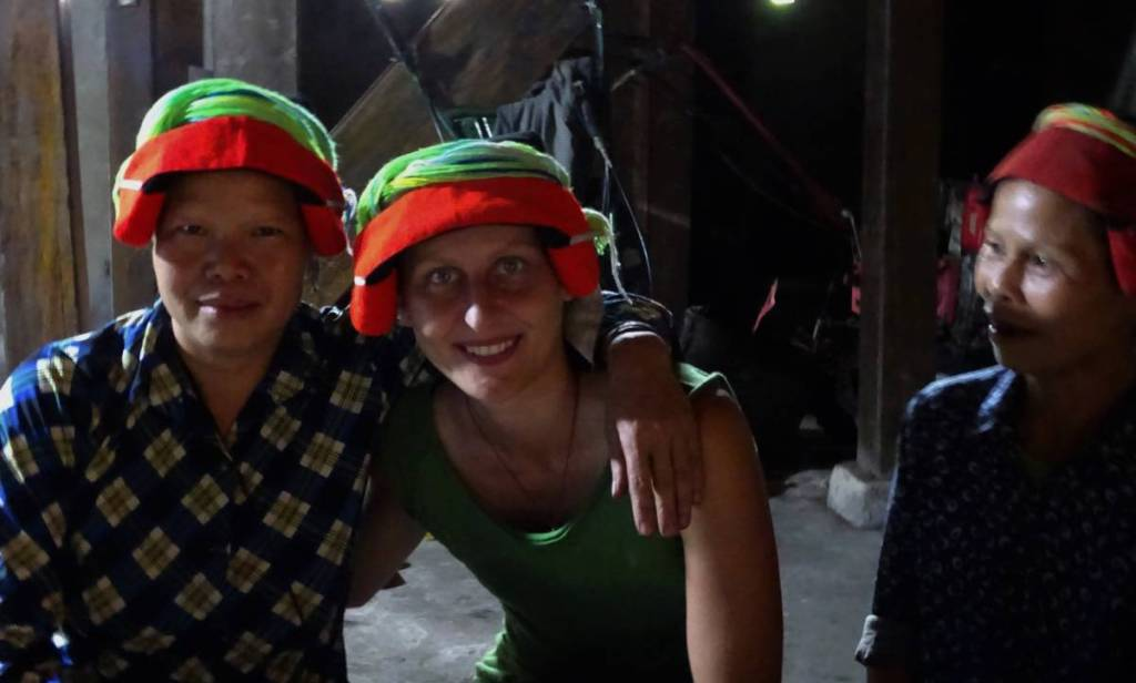 Two women from  Dao Ao Dai ethnic minority in their traditonal red-and-green headwear posing to the photo with the author
