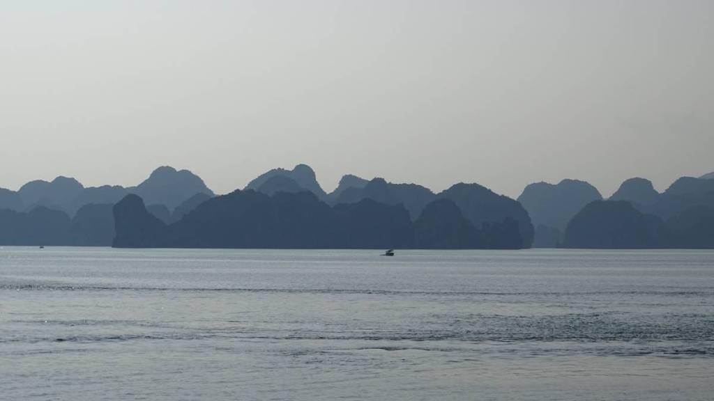 Silhouettes of irregularly, roughly shaped limestone islets on the horizon at Ha Long Bay.