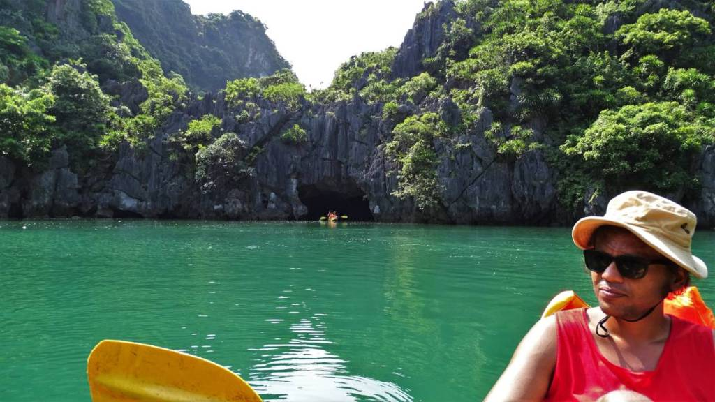 Sayak kayaking on green waters of the lagoon in Ha Long Bay, accessible only through a cave from where another kayak is just emerging