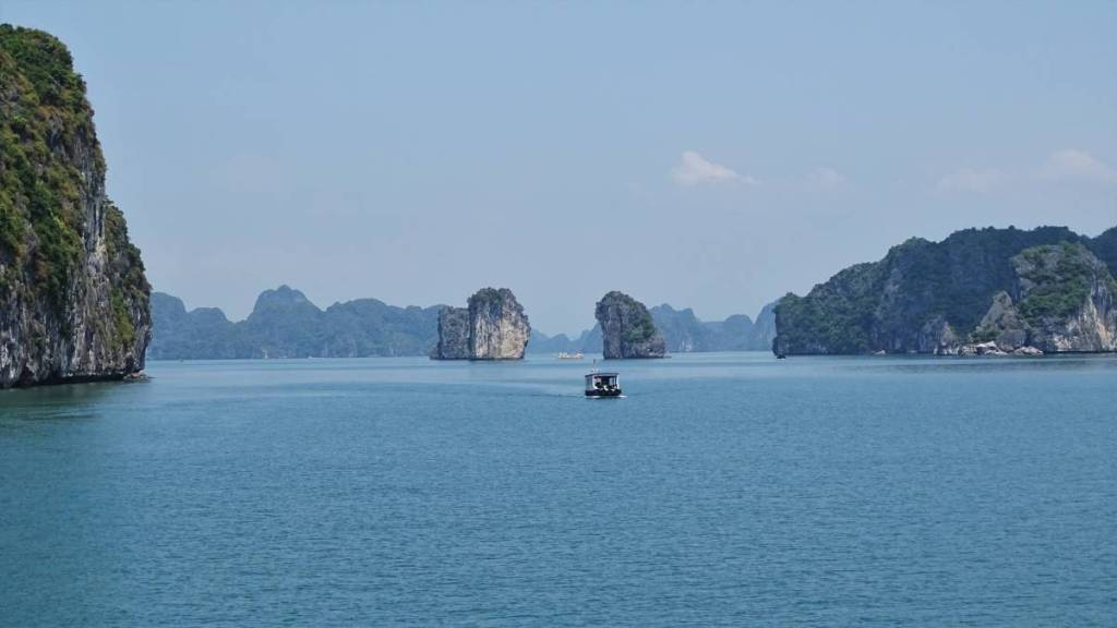 A small boat approaching two rocks resembling a gateway and the surrounding karst landscape of Ha Long Bay