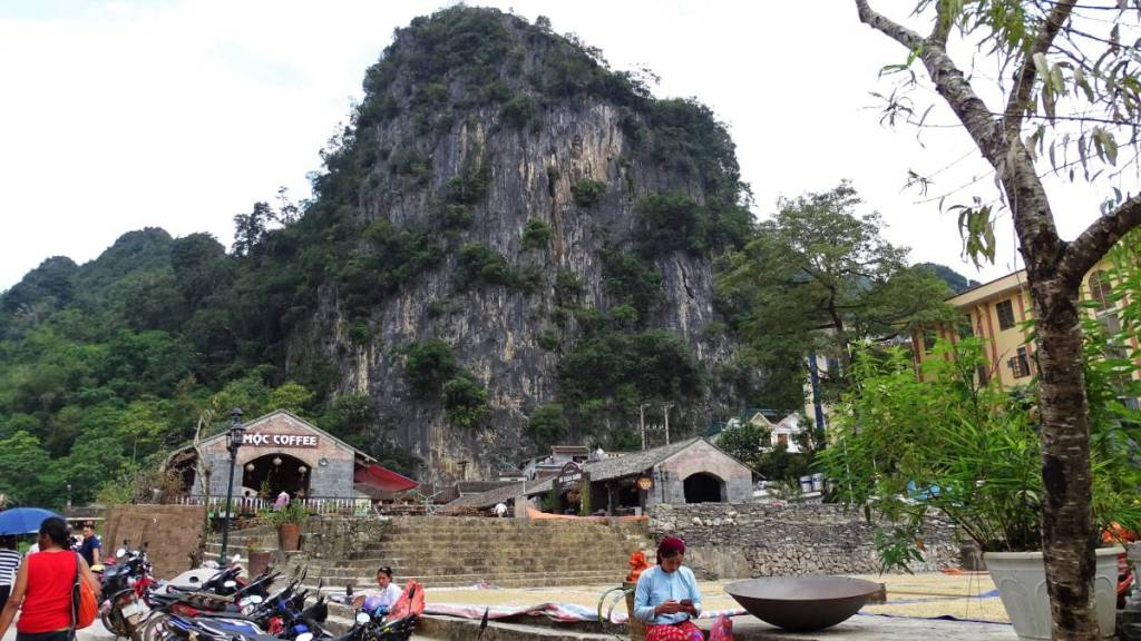 The Old Quarter in Dong Van: an elevated, stone square, stone and adobe buildings around it and karst rocks rising from behind