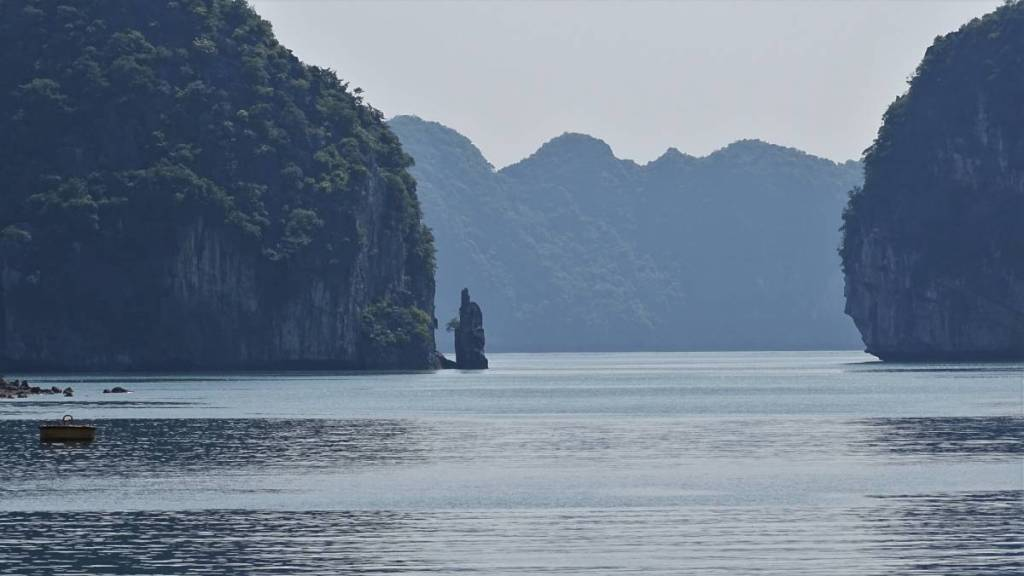 A narrow passage between two karst islets and more islands on the background in Ha Long Bay, Vietnam