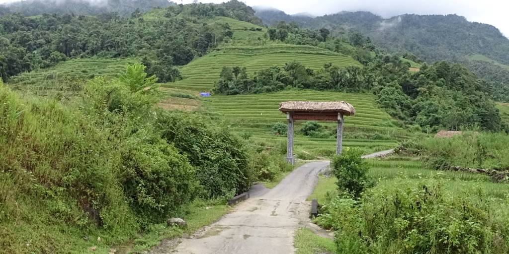 A narrow, tarmac path leading from Ha Giang to Lung Vai village set among the slopes half covered with forest, half covered with rice terraces