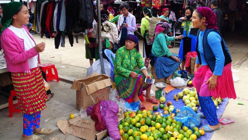 Women wearing colourful skirts on top of equally colourful trousers and headscarves chat at a makeshift stall selling fruit at the Sunday Dong Van market