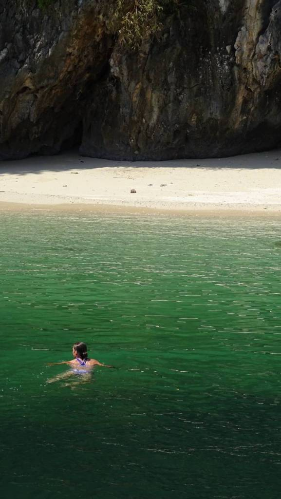 The author swimming in emerald green water towards a small white sand beach under the karst cliff in Ha Long Bay