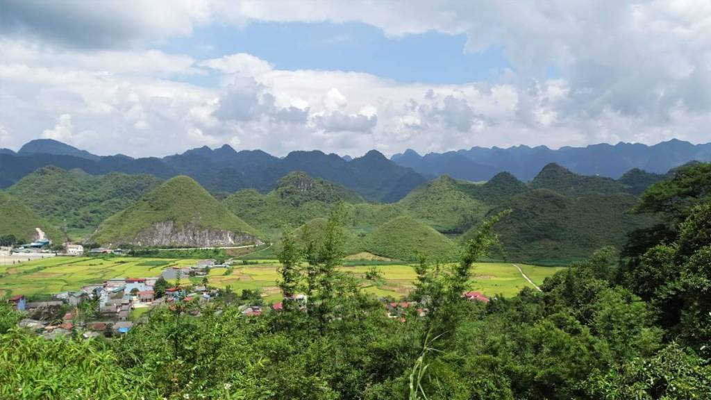 The Heaven's Gate on Ha Giang loop: two equally sized hills resembling female breasts and other conical hills springing up from the  green paddies with a comb-shaped higher mountains filling up the background