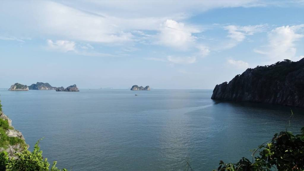 A view from Cat Ba island at the karst rocks rising from the sea and the cliffs of the Cat Ba island itself