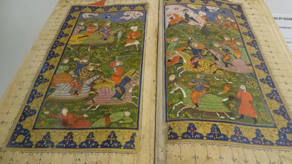 A detailed, colourful miniature depicting fight of warriors on horses filling up the whole page of the old book displayed at the Islamic Arts Museum in Kuala Lumpur