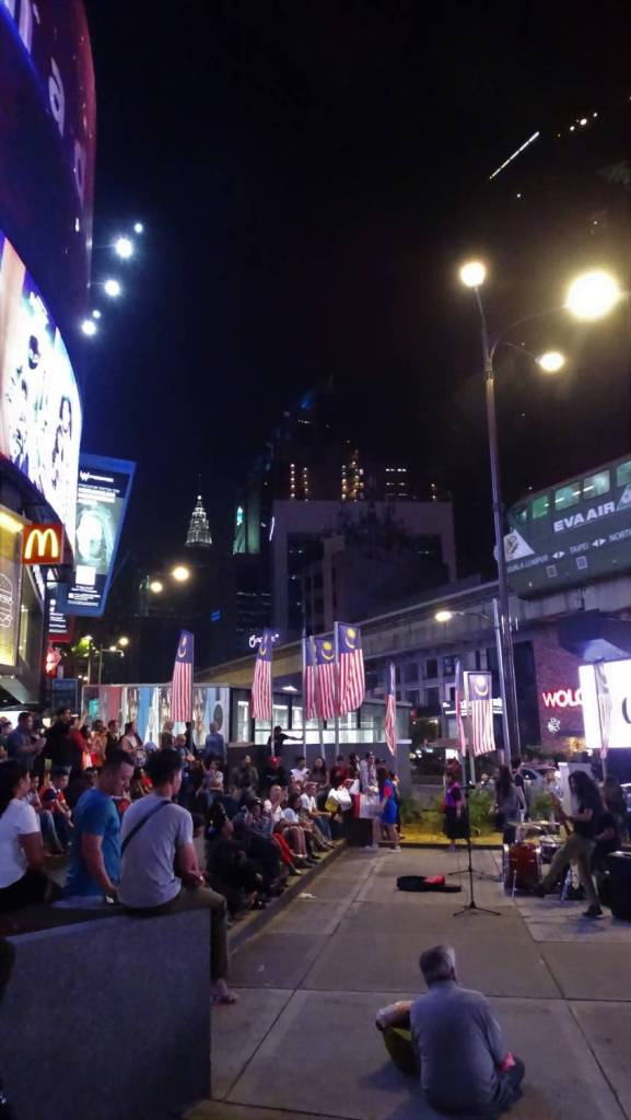 Night-time street performance at Bukit Bintag road in Kuala Lumpur: a crowd sits around the performer standing between monorail  and buildings decorated with LCD screens