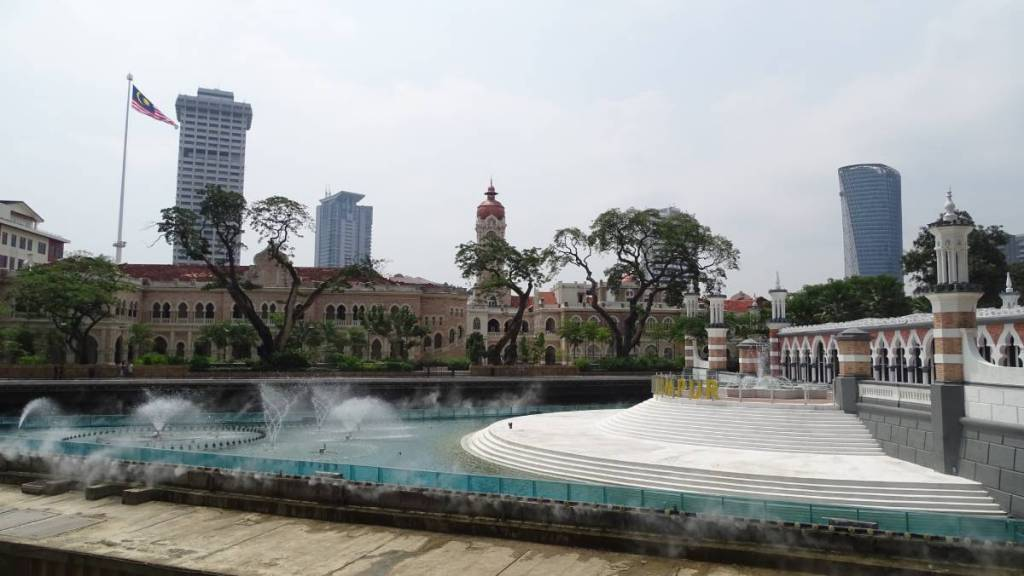 Confluence of Klang and Gomak rivers at the heart of Kuala Lumpur, the Masjit Jamek to the right, Sultan Abdul Samad building in the background and a flagpole with Malaysian flag beyond
