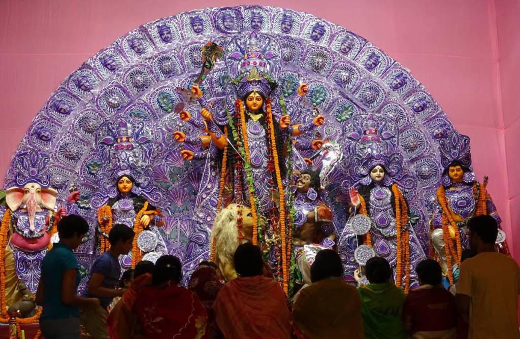 Women in saris gathered in front of the paper-mache altar of 10 handed goddess Durga  with her entourage of other deities as part of Durga Puja celebrations