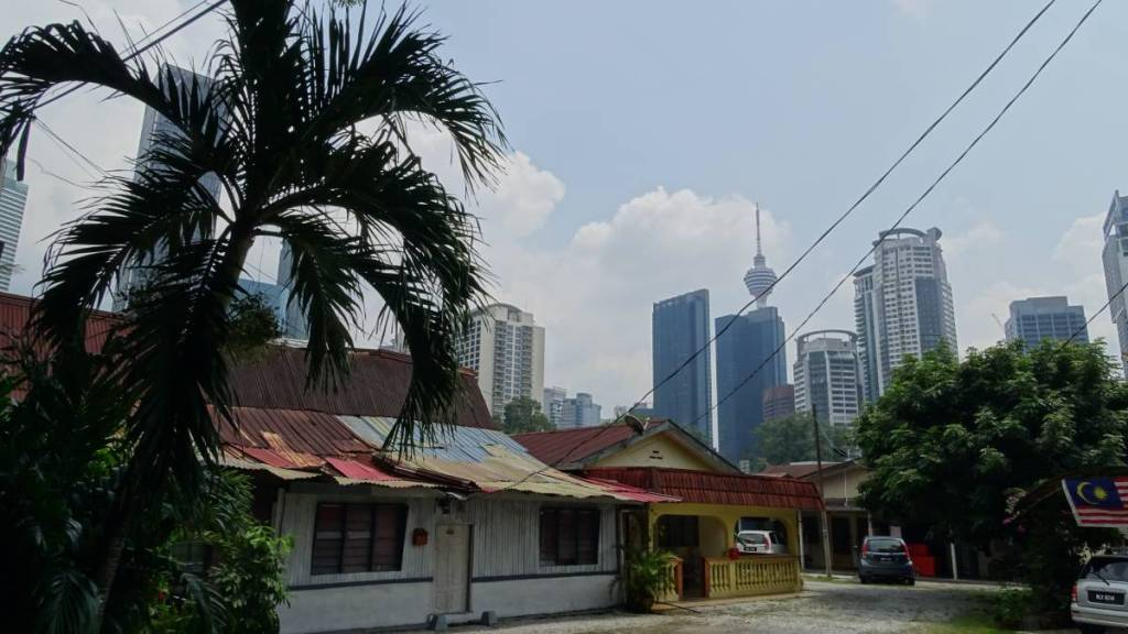 Traditional, simple wooden huts among banana trees in Kampung Bahru district of Kuala Lumpur, surrounded with skyscrapers