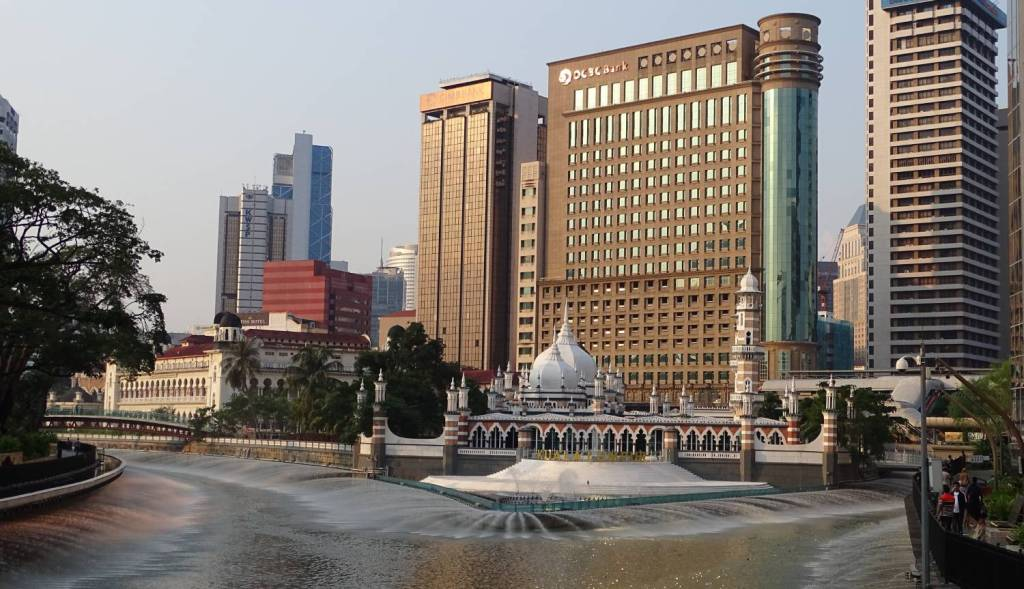 Klang river,  the national mosque and high-rise buildings in the background at Kuala Lumpur city centre