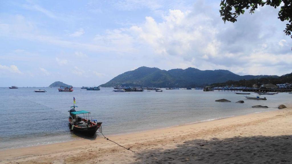 A long-tail boat moored on the sandy beach near Mae Haad pier, Koh Tao, Thailand