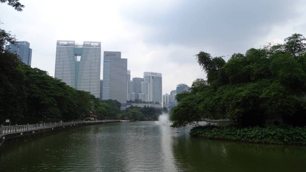 A ring of trees, a pond with fountains and the view at scyscrapers at the Lake Gardens in Kuala Lumpur