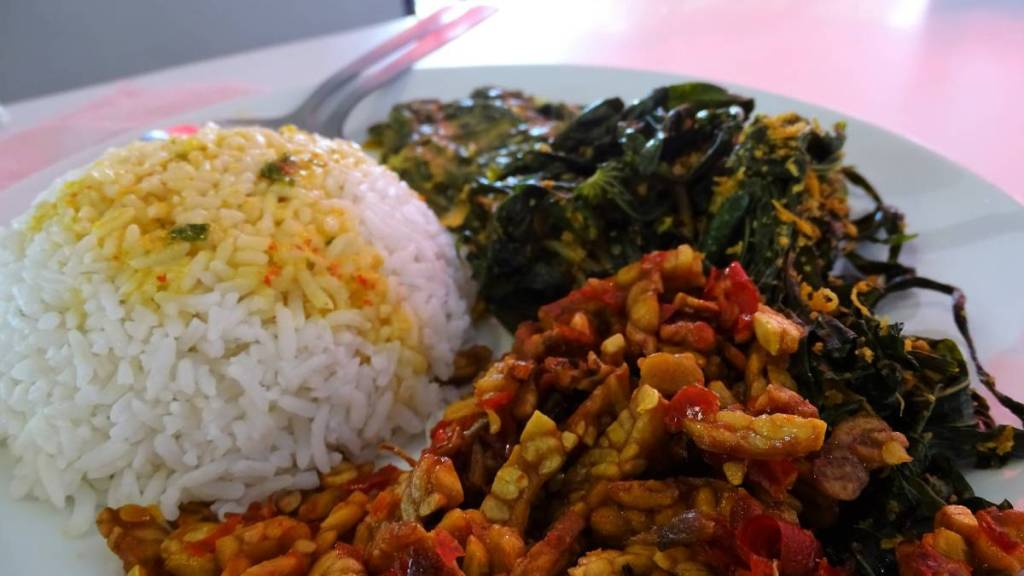 Malay buffet dishes: rice, greens and tempeh in tomato