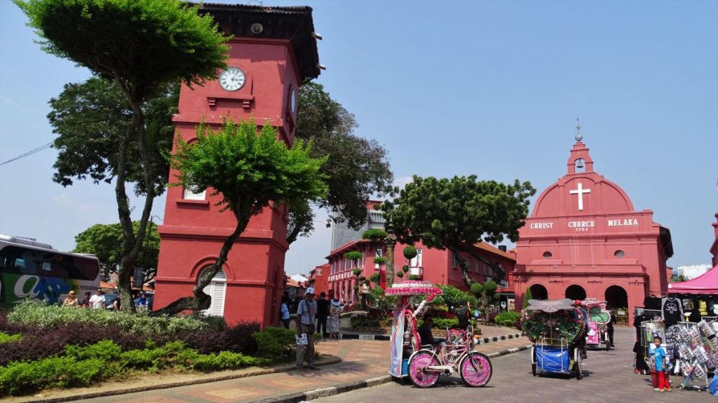 Dutch Square in Malacca: the colourful rickshaws stand in front of the red coloured clocktower, Christ Church and other colonial buildings