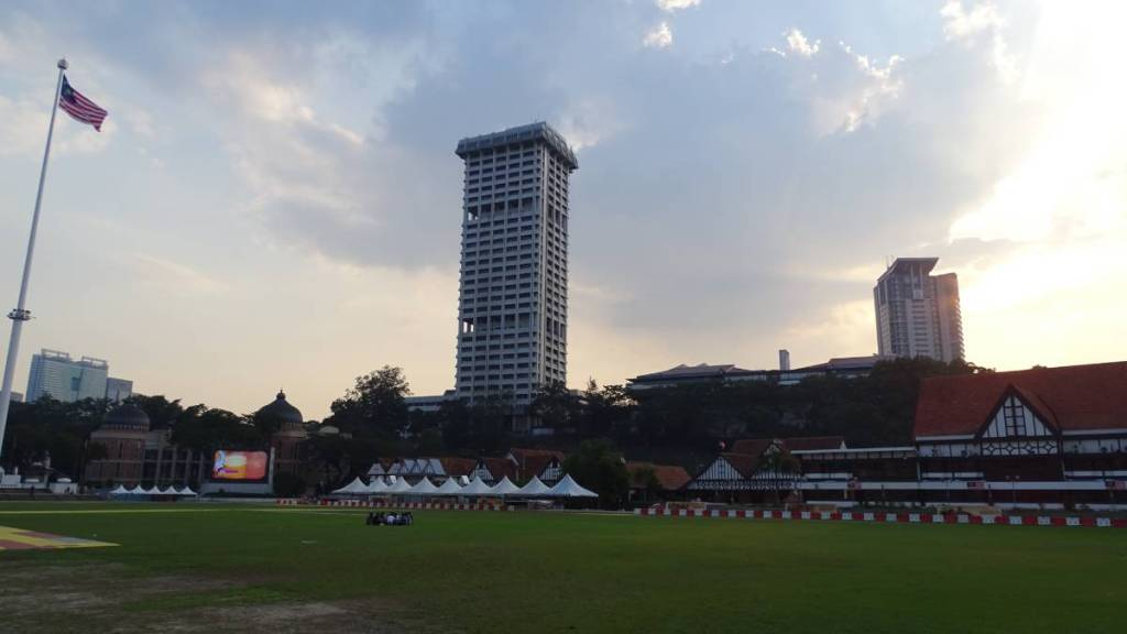 Green lawn of Merdeka Square in KL with a Malaysian flag on a high flagpost, mock-Tudor buildings of Selangor Club and high rise buildings in the background