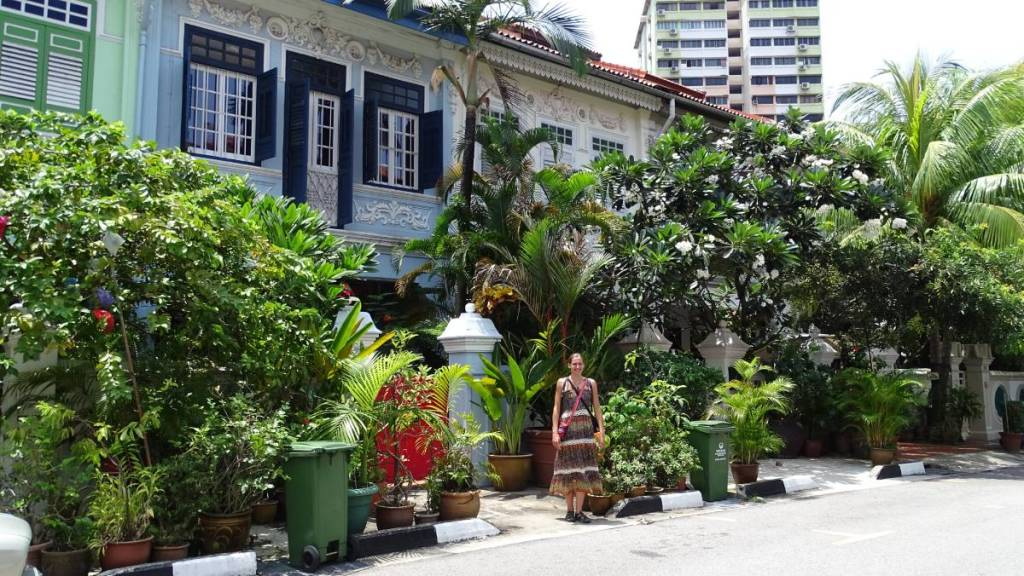 Author posing in a dress in front of old colonial style buildings with small gardens on a quiet street in Singapore