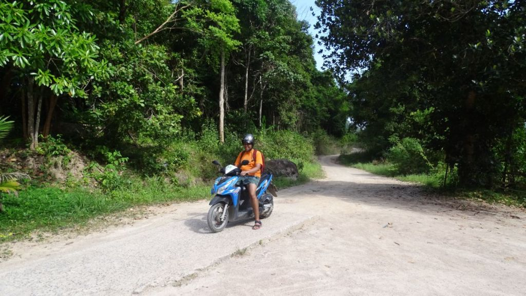 Sayak on the scooty in narrow, dart road in Koh Tao