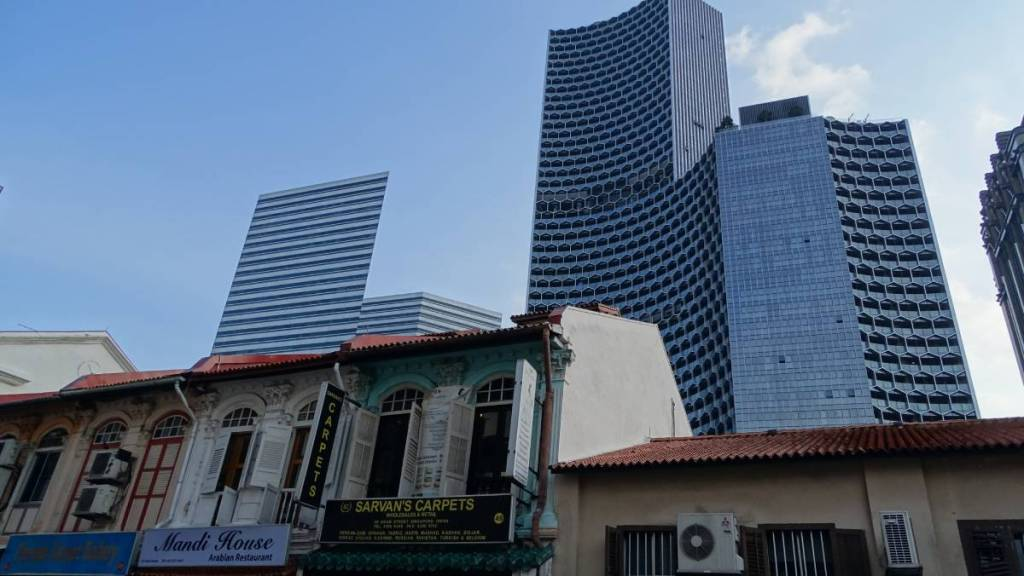 Nicely renovated and painted old colonial style houses and rising from behind them skyscrapers in Singapore