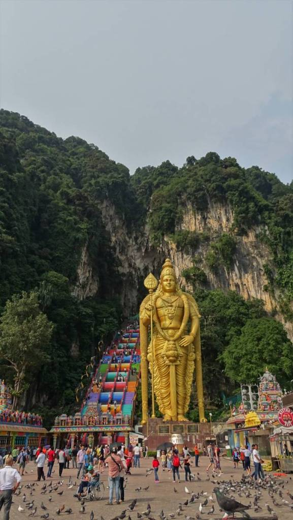 Visitors gathered in front of the gigantic godlen statue of standing god Siva and the colourful, steep steps leading up to the Batu Caves outside KL