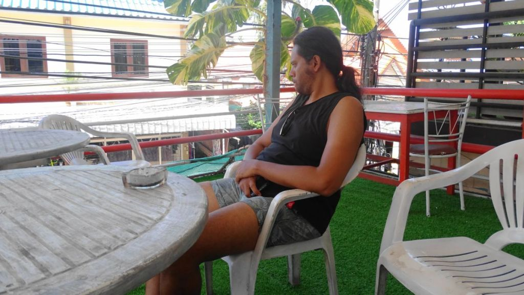 Sayak sitting in the open terrace of our guesthouse in Koh Tao