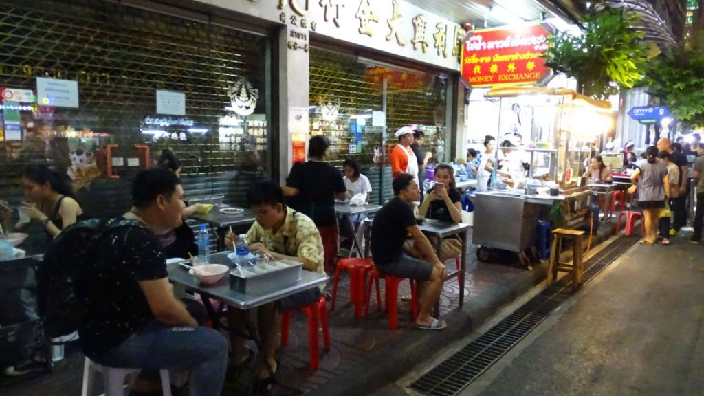 People eating at roadside eateries on the footpath of Yaowarat road, Bangkok at night