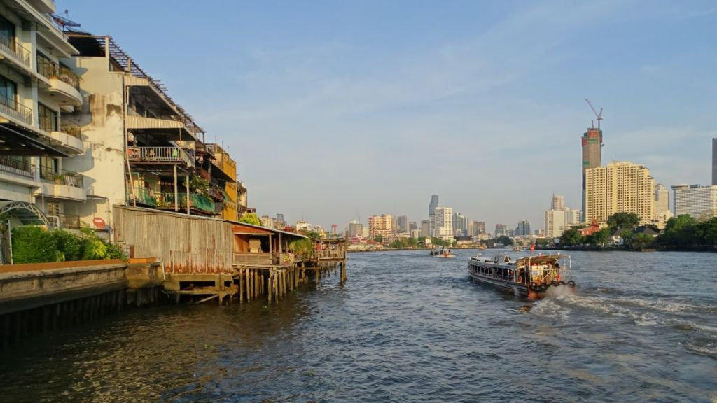 A passenger boat sailing through Chao Phraya river in Bangkok with few skyscrapers in the background