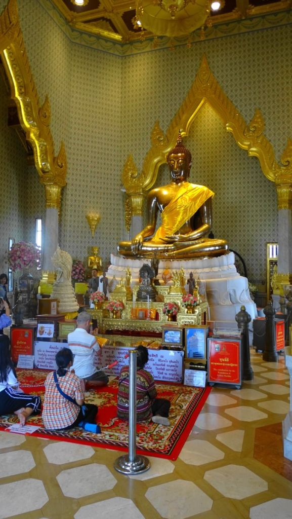 Devotees praying in front of the gold seated Buddha statue at Wat Traimit, Bangkok