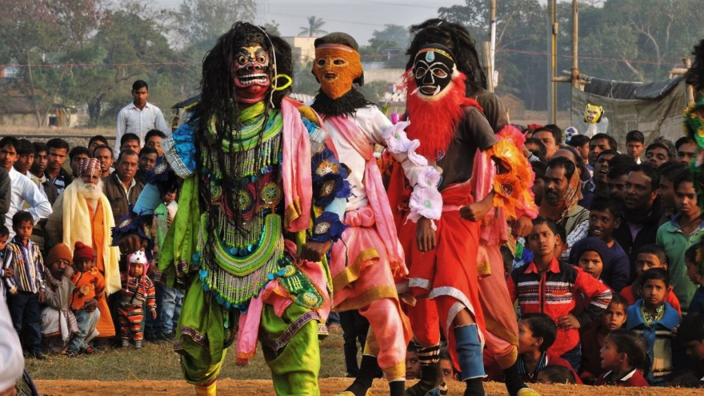 A crowd of local spectators watches Chhou dancers in their colourful costumes and coplex masks