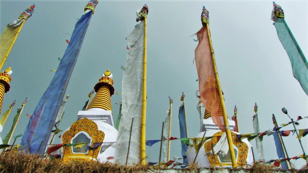 Golden-white stupas (conical Buddhist towers) interspersed with Buddhist flags on bamboo poles in Darjeeling