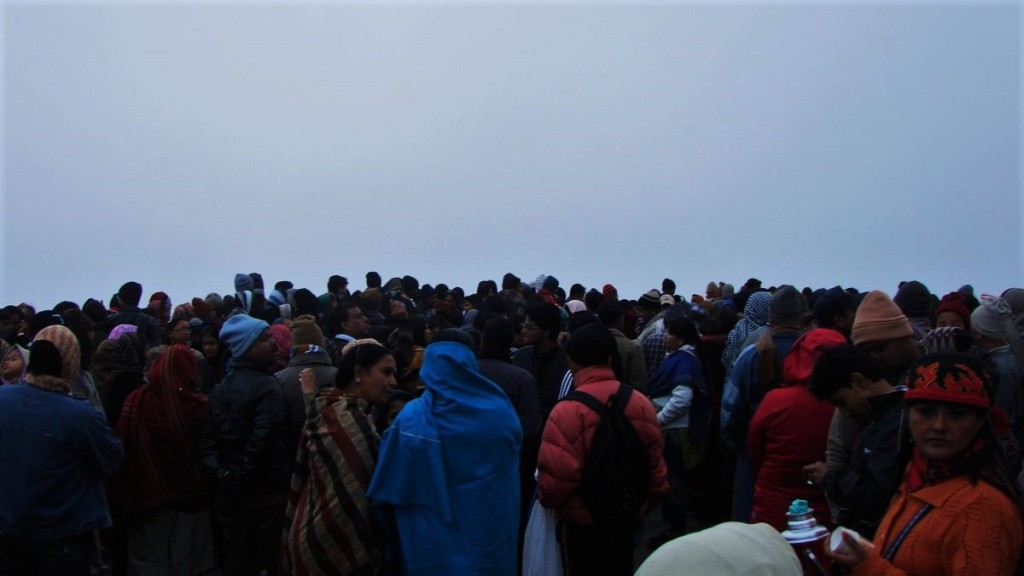 A crowd of Indian tourists wrapped up in shawls and and scarves gather at Tiger Hill in Darjeeling at dawn