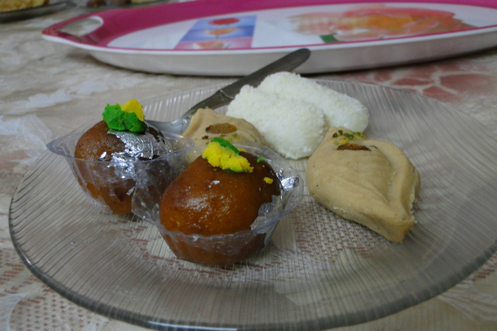 A plate full of Bengali sweets: round, brown ledikeni and conch shaped sandesh