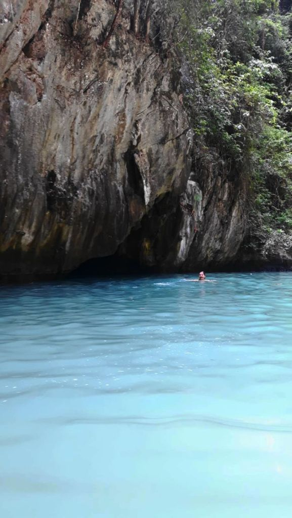 Weronika is swimming in the emerald lagoon, behind her the  entrance we swam through